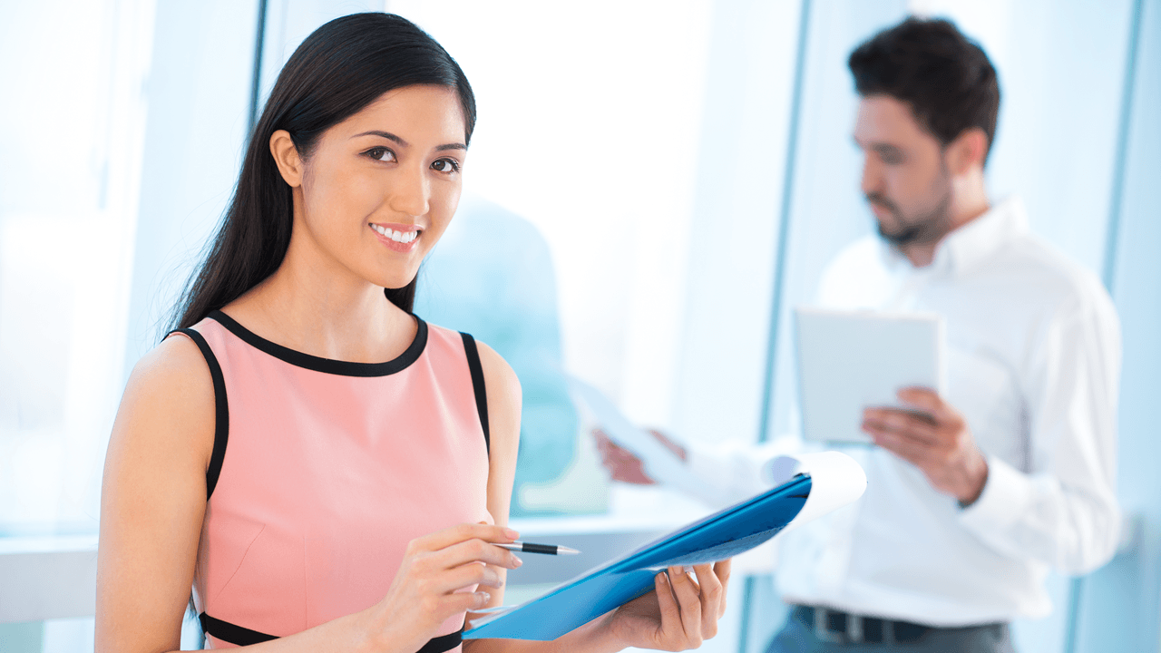 Women standing with IT compliance reports file paper